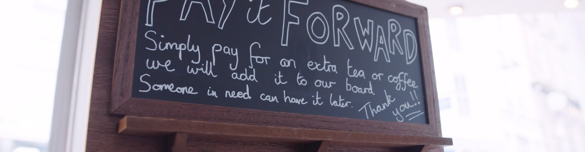 Chalk board in a cafe reads Pay it Forward