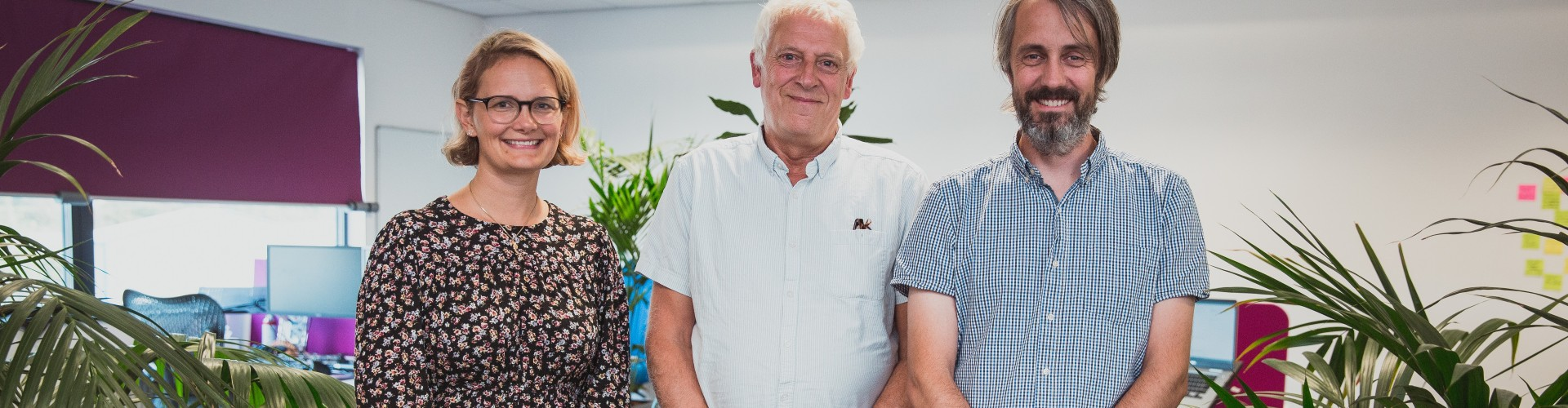 Three people in an office smiling at the camera