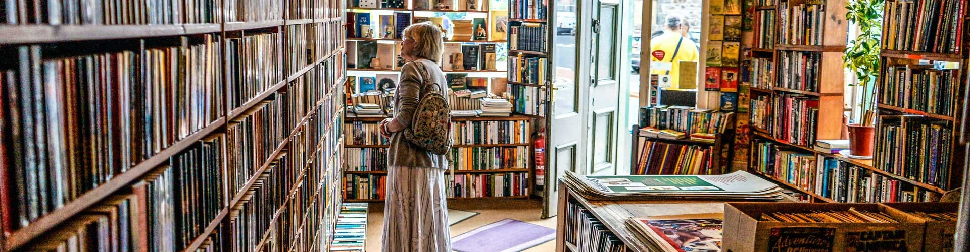 woman browsing shelves in book shop