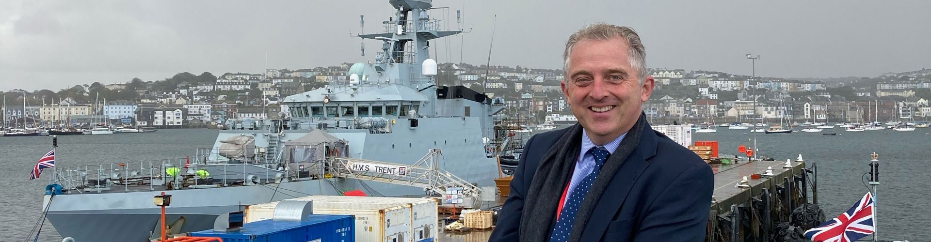 miles carden in front of navy ship in Falmouth