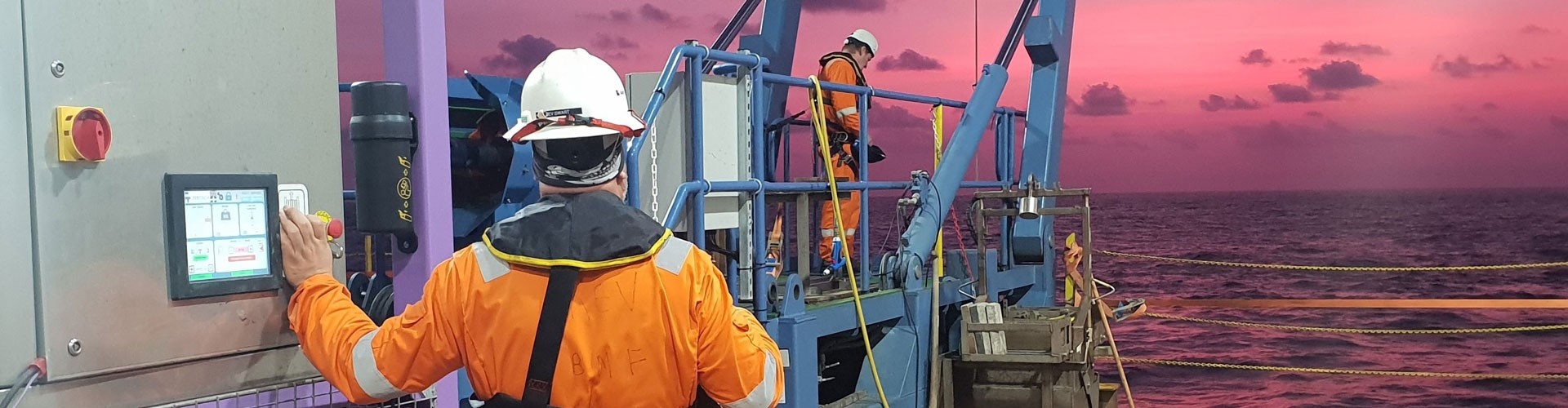 men working on a platform at sea with sunset in background