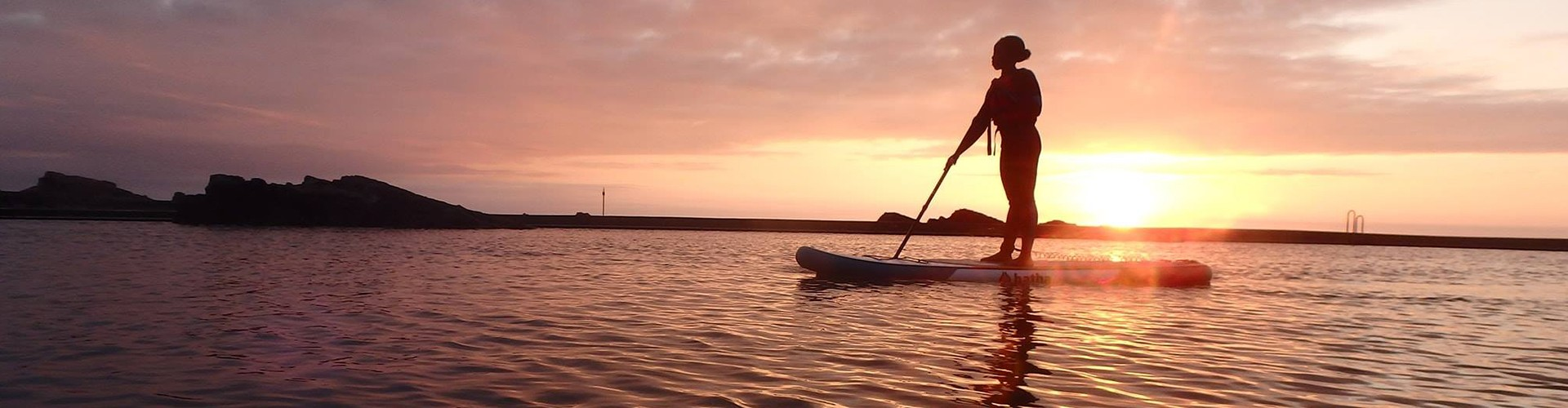 Person on a paddleboard at sunset at Bude sea pool