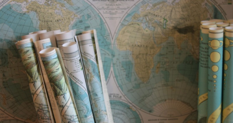 rolled up maps in front of a map of the world