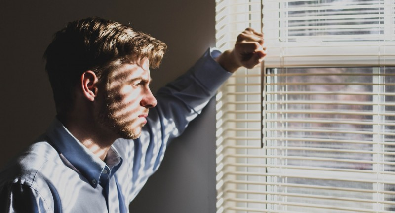 sad man looking out of window
