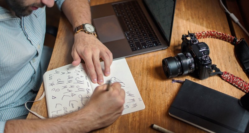 man drawing with camera and laptop on table