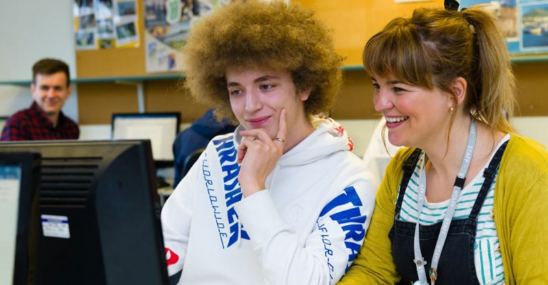 two youths looking at a computer screen smiling