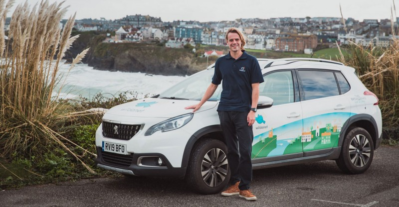 wildanet company car and employee with Cornish sea cliffs and town background