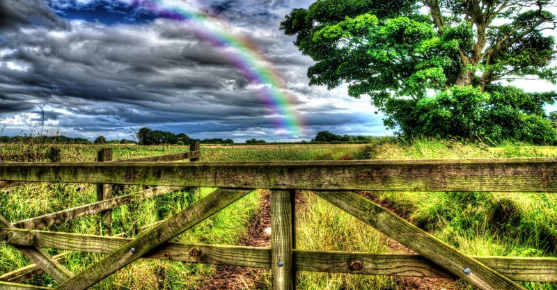 rainbow over gate in rural england