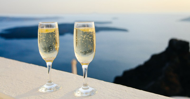 two glasses of champagne overlooking sea in distance
