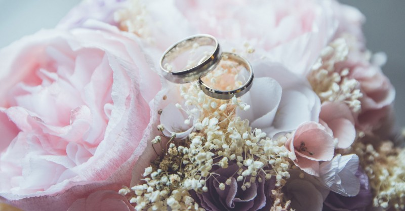 wedding rings on top of pink flower bouquet