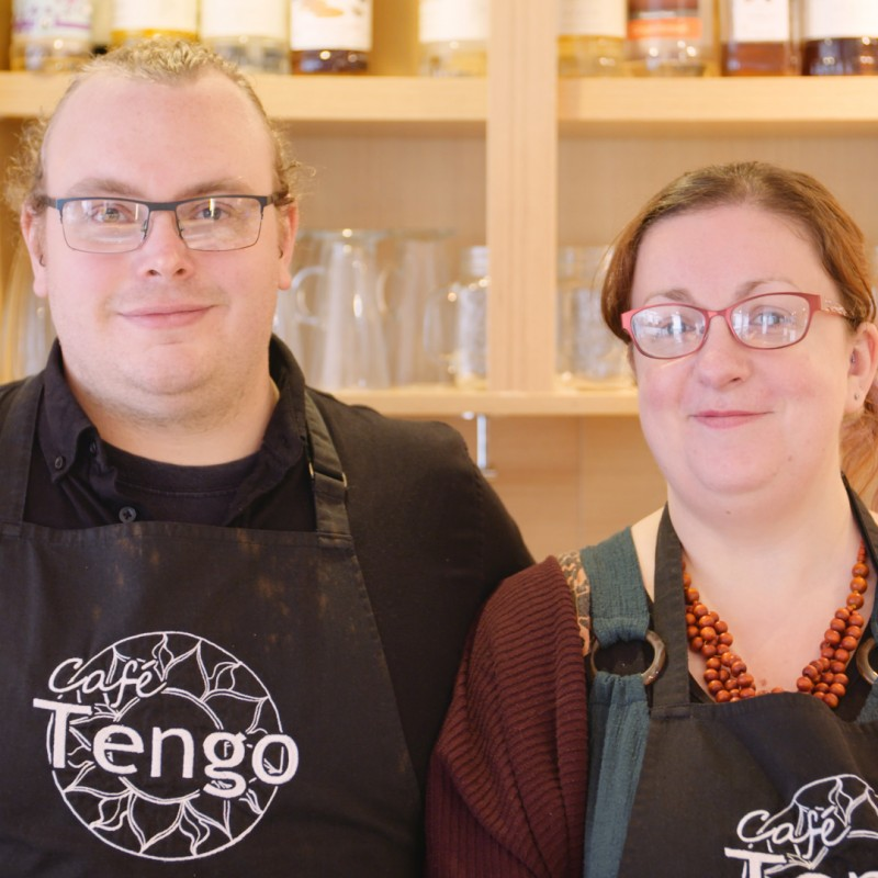 Man and woman in a cafe wearing aprons with the word Tengo on them